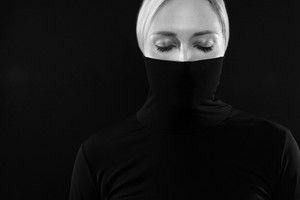 Black and white portrait of woman hiding face in black turtleneck