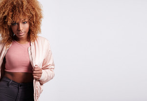 black blonde woman in pink jacket with afro hair