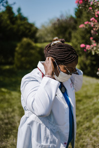 Black female physician putting on face mask