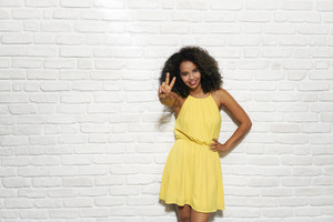 Black girl looking at camera and doing peace sign with hand or V sign with fingers. Slow motion, copy space