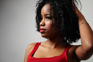 black woman in red dress with bright red lips and curly hair