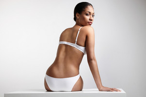 black woman in underwear from the backside looking at camera