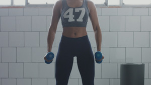 black woman portrait during weight training closeup with foucus on hand with weight moving to a camera