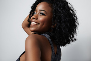black woman touches her curly hair and smiling