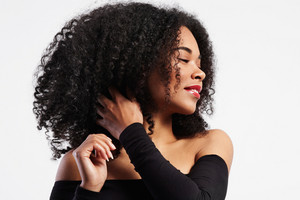 black woman touches her curly hair