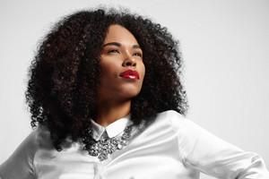 black woman watching aside. curly hair red lips