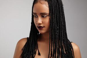 black woman watching aside showing her braids