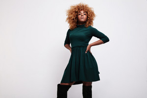 black woman wears a green dress, blonde hair