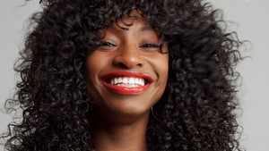 black woman wide smiling with lips with red lipstick