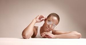 black woman with a short haircut in studio shoot closeup wearing glasses cobra