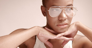 black woman with a short haircut in studio shoot closeup wearing glasses cobra