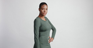 black woman with a short haircut in studio shootsmiling and wearing dress