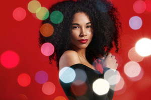 black woman with big afro hair and christmas holiday bokeh lights around