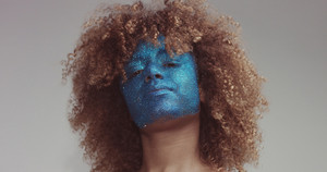 black woman with blond hair and blue glitter face makeup portrait