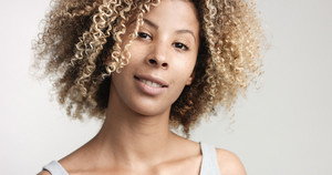 black woman with curly afro hiar and freckles portrait