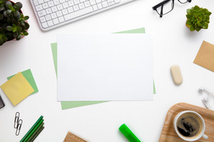 Blank Papers Surrounded With Office Supplies On White Desk