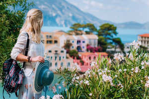 Blond beautiful woman enjoying view of colorful tranquil village Assos on sunny summer travel vacation day. Visiting Kefalonia, Greece