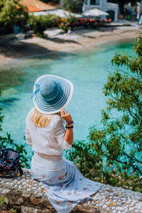 Blond beautiful woman with blue sunhat and white clothes sitting in front of blue bay of colorful tranquil village Assos, Kefalonia, Greece