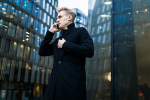Blond-haired manager wrapped up in black coat standing at modern office building and calling to his client on phone, low angle view