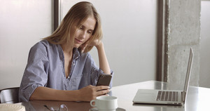 Blond model in a relaxed button-up shirt switches between her laptop and her phone at work