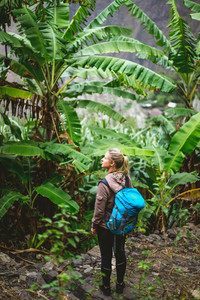 Blond yong women with blue backpack admire banana plantation on the trekking route to paul valley on santo antao island, cape verde