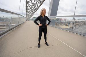 Blonde Female Beauty in Black Workout Wear Standing At Modern Bridge In City