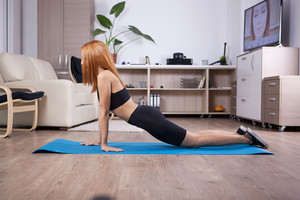 Blonde girl doing cobra yoga pose in her house. Healthy body healthy soul.