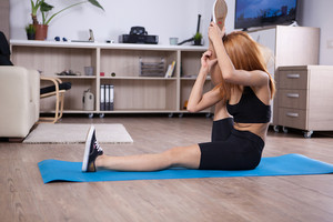 Blonde girl stretching her hamstring during her yoga time. Fit young woman .