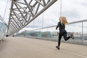 Blonde woman runner in black workout outfit in modern city environment