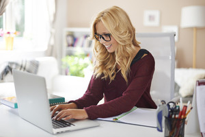 Blonde woman using laptop at home