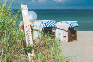 Blue colored roofed chairs on sandy beach in Travemunde, Germany. Welcome balloons