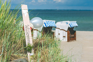 Blue colored roofed chairs on sandy beach in Travemunde, Welcome balloons. Germany