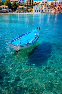 Blue fishing boat in the emerald azure rippled sea water bay in Assos village, Kefalonia island, Greece