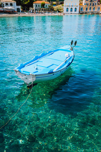 Blue fishing boat in the emerald azure rippled sea water bay in Assos village, Kefalonia island, Greece