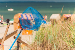 Blue hand net on the beach. Roofed wooden chairs on sandy beach in Background. Travemunde, Germany