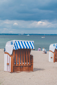 Blue striped roofed chairs on empty sandy beach in Travemunde. Blurred people in background