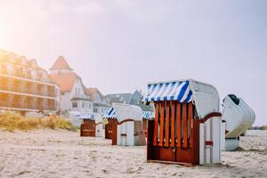 Blue striped roofed chairs on sandy beach near resort Travemunde in sun light in low season. Germany