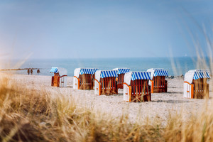 Blue striped roofed chairs on sandy beach on sunny day framed by dune grass in Travemunde. Germany