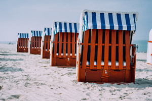 Blue striped roofed wooden chairs stands in line on sandy beach on sunny day. Travemunde, Luebeck, Germany