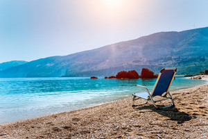 Blue sunchair on picturesque pebble beach, Kefalonia island, Greece. Travel relax vacation concept