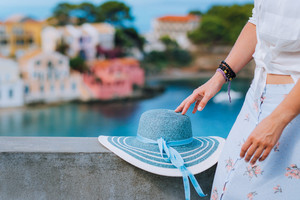 Blue sunhat laying on the wall. Tourist woman enjoying view of colorful tranquil village Assos on sunny day. Stylish female visiting Kefalonia in summer time on Greece travel vacation
