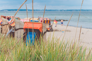 Blurred colorful roofed chairs on sandy beach in Travemunde. Germany