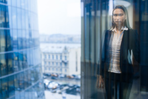 Blurred female figure inside moderm multi-storey office center