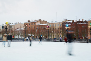 Blurred human figures skating on ice-rink in urban environment
