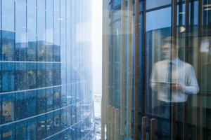 Blurred reflection of young businessman inside office building