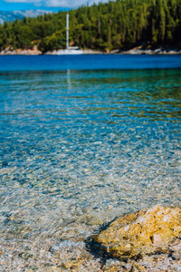 Blurry sail boat docked alone in emerald hidden lagoon among picturesque mediterranean nature Ionian Islands, Greece