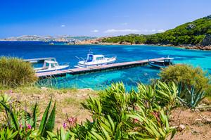 Boats at pier in emerald green mediterranean sea water, coast of Maddalena island, Sardinia, Italy