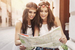 Boho girls looking for right way at map