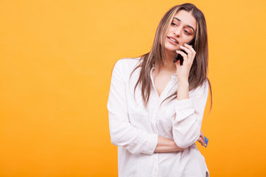 Bored girl in white shirt talking on the phone and holding credit card over yellow background. Casual dressed