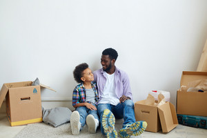 Boy and his father having rest on the floor of new flat after relocation